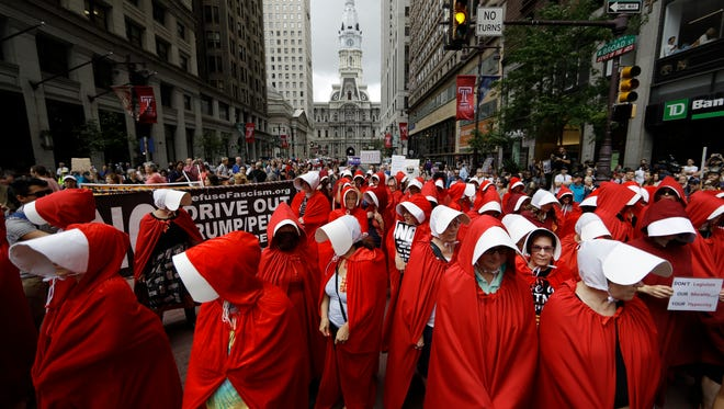 "Protesters, in view of City Hall, center, dressed as characters from ""The Handmaid's Tale,"" demonstrate against Vice President Mike Pence's visit to the Union League in Philadelphia, Monday, July 23, 2018. (AP Photo/Matt Rourke)"