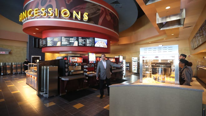 Regional operations manager Troy McDaniel gives a tour of the popcorn and concession stand at the new CMX theater.