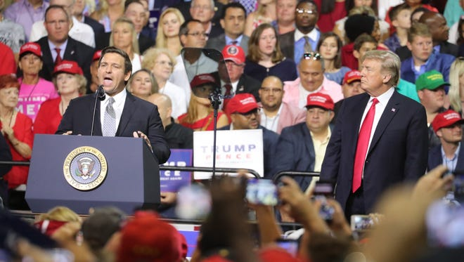 Florida GOP candidate Ron DeSantis speaks as President Donald Trump looks on Tuesday during a rally in Tampa.