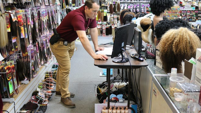 Greenville Police Department investigator Payton Loyd reviews surveillance video from a recent shoplifting at a beauty supply store in Greenville.