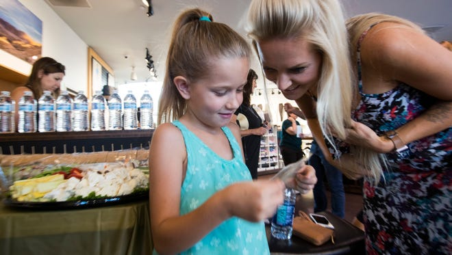 Rylie Hood, 8, and her mother Jessica Hood look at a photo of Rylie during a workshop aimed at improving self-confidence. The project is a body empowerment program teaching mindfulness, acceptance and self-care skills. Lululemon in Palm Desert is also participating in this program.
