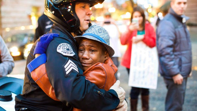 Portland police Sgt. Bret Barnum, left, and Devonte Hart, 12, hug at a rally in Portland, Ore., where people had gathered in support of the protests in Ferguson, Mo., on Tuesday, Nov. 25, 2014,