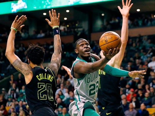 Boston Celtics' Jabari Bird (26) drives for the basket past Atlanta Hawks' John Collins (20) during the fourth quarter of an NBA basketball game in Boston, Sunday, April 8, 2018. (AP Photo/Michael Dwyer)