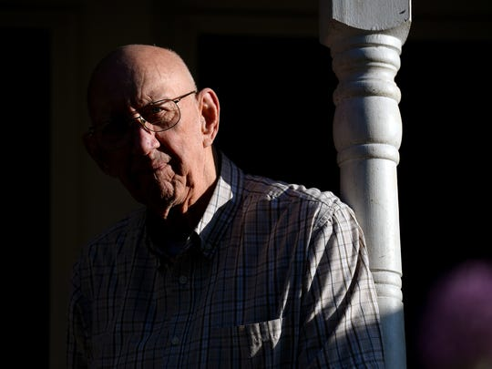 "Robert Flory stands on his porch in the early evening sun Monday at his home in Holt. Flory, 84, is a Korean War veteran and recently received a Purple Heart he thought was stolen along with a Bronze Star and other medals he didn't know he qualified for. Even though he was wounded in battle, he said he ""didn't give a rip"" for the medals and that there were others who sacrificed more than he did."