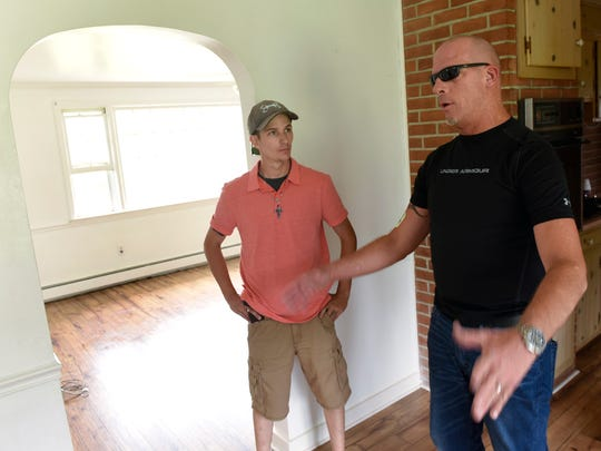 Drew Reed, left, and John Lloyd take a break Friday from refurbishing a place they are transforming into Noah's House, a substance abuse recovery home.