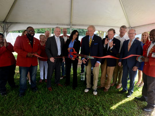 Members of the Jackson Chamber Red Coats are joined with Mayors Jerry Gist and Jimmy Harris, along with others as COO of Aldelano, Nicole Smith, cuts a ribbon during the announcement of their expansion in Jackson.