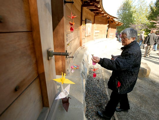 A visitor hangs a strand of origami cranes next to