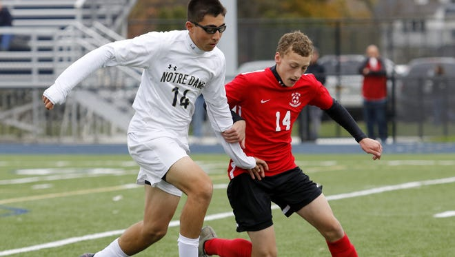 Notre Dame's Aidan Sharma and Spencer-Van Etten's Bryant Sexton battle for possession Saturday during a Section 4 Class C boys soccer quarterfinal at Brewer Memorial Stadium.