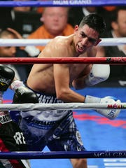 Leo Santa Cruz (blue/white trunks) and Jose Cayetano (black trunks) box during their featherweight bout May 2, 2015, at MGM Grand Garden Arena in Las Vegas.