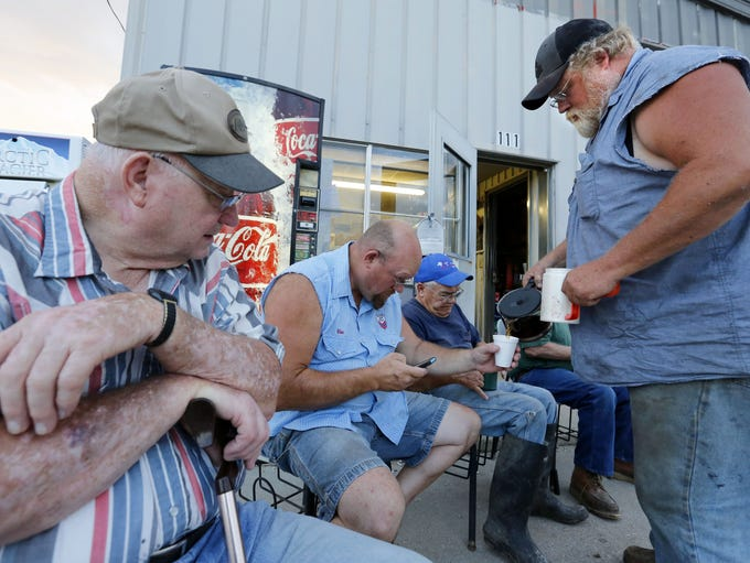 Randy Needham, right, pours coffee for Mike Fry during a daily gathering outside Frank's Service in Arispe.  Union County men gather there to begin their day with fellowship.  The remote, weathered station is one of the few remaining commercial businesses in the southern Iowa town of about 100.