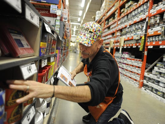 A Home Depot employee straightens up merchandise in the paint department of the west Reno store on Wednesday, Jan. 25, 2012.
