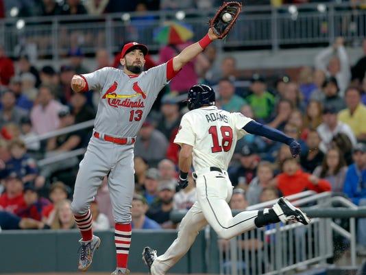 Atlanta Braves pinch hitter Lane Adams (18) is safe at first base as St. Louis Cardinals first baseman Matt Carpenter (13) handles a high throw from second baseman Kolten Wong in the sixth inning of a baseball game Saturday, May 6, 2017, in Atlanta. (AP Photo/John Bazemore)
