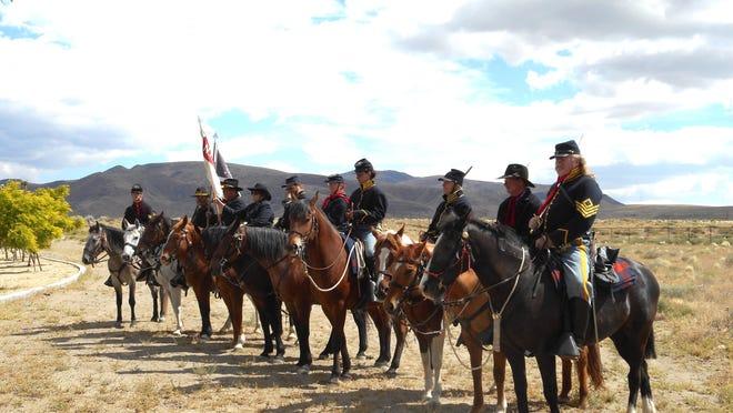 1st Battalion Volunteer Cavalry reenactors pose after mock cavalry charge at Trooper statue dedication.