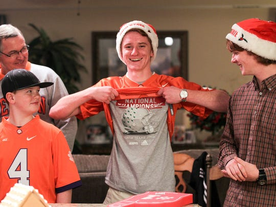 Bob King, left, watches Brent Merlo show off an Ohio State 2013 National Championship T-shirt underneath a Clemson jersey with Brent's brothers Derrick, left, and Chris, right, in a conversation Friday in the Merlo home dining room in Anderson.
