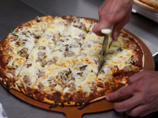 A fresh pizza is sliced before being served at House of Pizza in downtown St. Cloud in this 2017 photo.