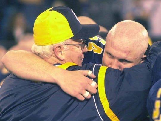 Grand Ledge Head Coach Pat O'Keefe hugs Nick Jensen