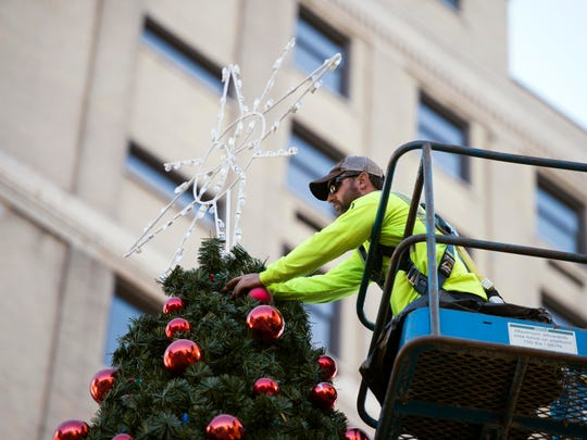 Chris Bowman of City of Knoxville's Public Service Department, places ornaments on the Downtown Christmas Tree at Krutch Park on Thursday, November 17, 2016. Bowman has decorated the tree for the past four years.