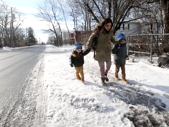 Ashlee Delgado walks with her sons.