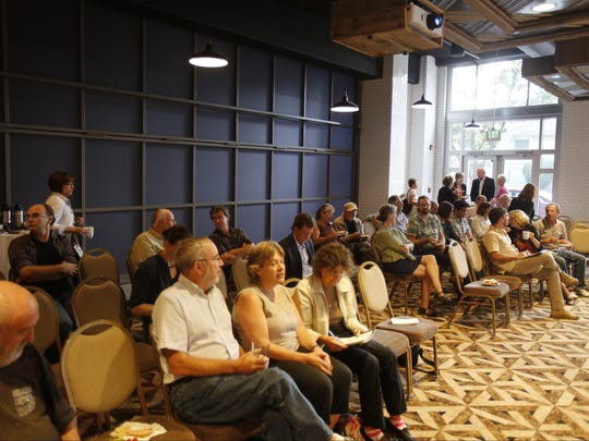 A small crowd of local residents and officials filled the back room of Coltivare for a meeting regarding changes to a proposed 11-story structure downtown.