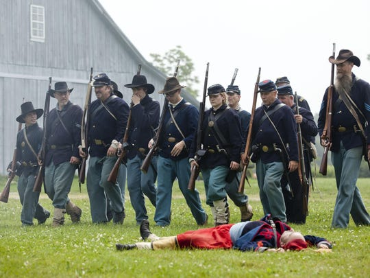 Union soldiers advance past a fallen Confederate during