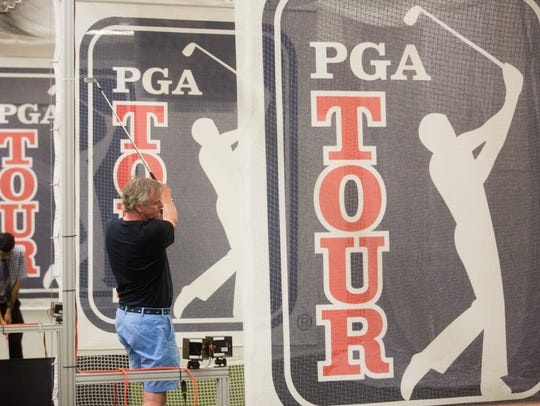 Golf enthusiasts try out clubs at the several indoor