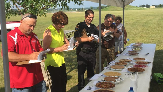 Judges evaluate the entries at the pie baking contest hosted as part of Richmond's 125th anniversary celebration Tuesday at Centennial Park.