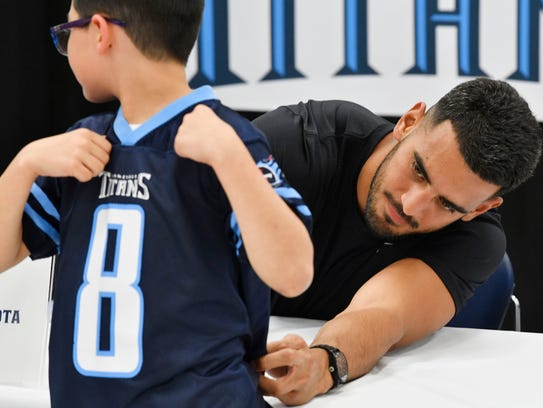 Titans QB Marcus Mariota signs a jersey for a young