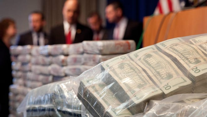 Sacks of money worth $2 million, and 154 pounds of heroin, left, worth at least $50 million, are displayed at a Drug Enforcement Administration news conference in New York on May 19, The DEA called the heroin seizure its largest ever in New York state. Officials said on Tuesday that most of the drugs were found in an SUV in the Bronx following a wiretap investigation.
