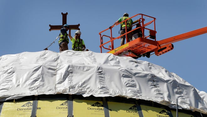 FILE- In this Aug. 10, 2017 file photo, construction workers adjust a temporary cross on the St. Nicholas National Shrine in New York. Work on the Greek Orthodox church destroyed in the Sept. 11 attacks next to the World Trade Center memorial plaza has been temporarily suspended by the construction company. It comes amid financial difficulties and questions over how funds have been managed.