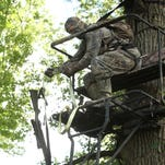 Before climbing the ladder to his tree stand , hunter Corey Woodby ties his slug gun to a haul line, which allows him to safely raise the firearm once he is safely seated and strapped to the bench some 20 feet above ground level.