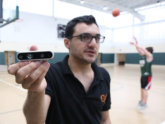 Matt Werner holds up the small sensor that is placed above the basket, during a demonstration of the RSPCT shooting software in the gym at Solomon Schecter School in Hartsdale Aug. 1, 2018.