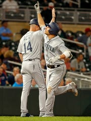 Seattle Mariners first baseman Danny Valencia (26) celebrates with third base coach Manny Acta after hitting a home run against the Minnesota Twins in the eighth inning at Target Field.