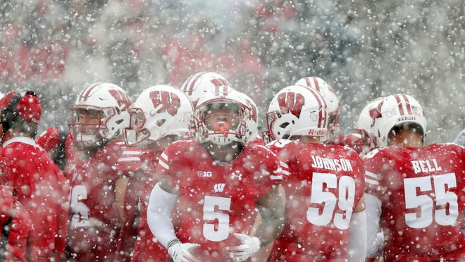 Wisconsin players huddle during a snowy game against Illinois in 2018. Weather conditions in parts of the country might be more frigid in a college football season that begins in February.