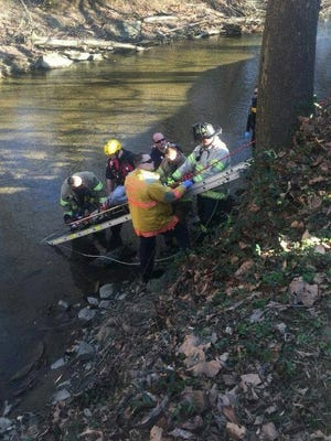 Emergency responders are seen rescuing a 73-year-old man who fell into Mill Creek on Monday.