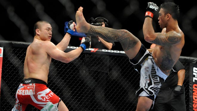 Brad Tavares attempts a high kick to Dongi Yang during a match in 2012. Tavares is among the number of fighters hoping to dominate at 185 pounds.