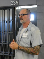 "David Buckridge, of Canton, describes how he and fellow inmates created the props, such as the jail cell behind him, for their performance of ""Shawshank Redemption"" Tuesday, Oct. 20, at Ross Correctional Institution."