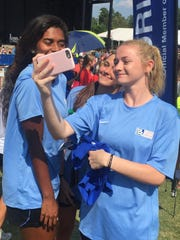 From left, Ashley Blanchard, Lauren Arrabito and Haley Knowles, members of the Tampa Bay United U19 girls team, take a selfie in front of the Florida banner during the opening ceremonies for the US Youth Soccer Region III Championships Thursday at Heritage Park in Simpsonville.