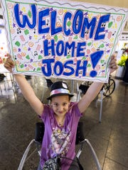 "Aeryn Miller, 10, Indianapolis, holds up the ""welcome"" sign that she made to greet Indy's latest celebrity back home. Josh Kaufman arrived back in Indianapolis Thursday, May 22, 2014, to a crowd of fans at Indianapolis International Airport."