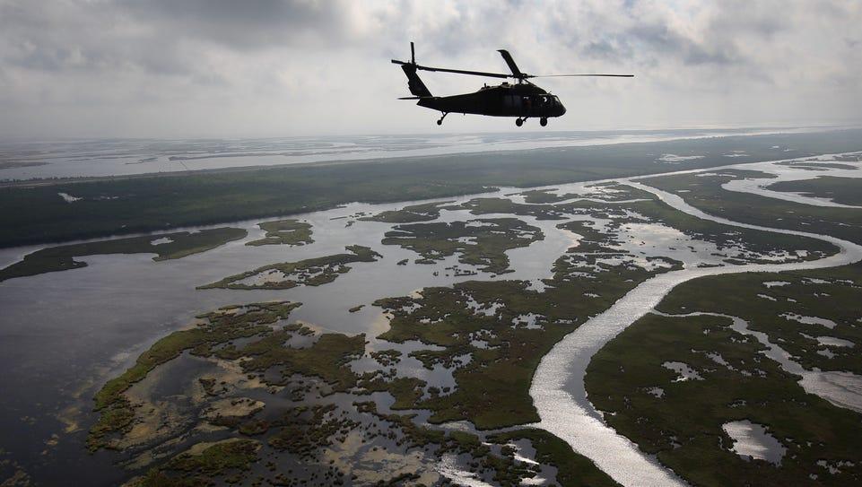 A Louisiana National Guard blackhawk flies over marshland