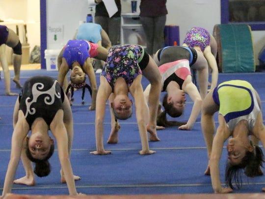 Elmira Gymnastics Club members stretch during a recent