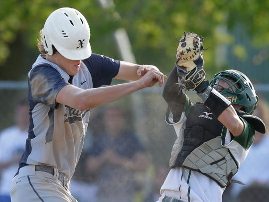 Xavier High School's Matt De Young, left, plows into Freedom High School's Kody Theobald along the third base line during their WIAA Division 2 regional semifinal baseball game Wednesday in Freedom.