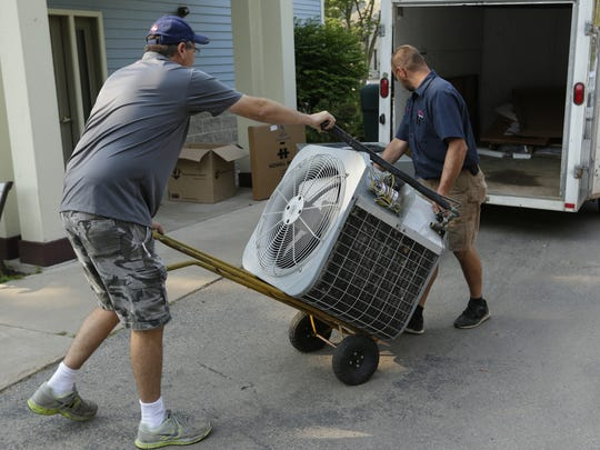 Mike Madison and Dan Kasuboski of Brewer Heating and Cooling remove the old air conditioner Wednesday, August 2, 2017, at the Christine Ann Center in Oshkosh. The center received donations through the community and businesses to fix the most needed of the problems that plagued the building. An air conditioner was donated by Design Air of Kimberly and installed by Brewer Heating and Cooling of Ripon.