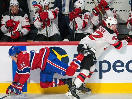 Montreal Canadiens right wing Michael McCarron (34) checks New Jersey Devils Nathan Bastien during the first period of a preseason hockey game, Thursday, Sept. 21, 2017 in Montreal.