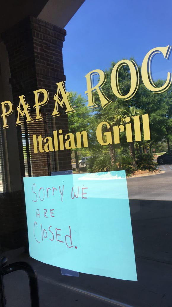 A closed sign hangs on the door of Papa Roc's Italian