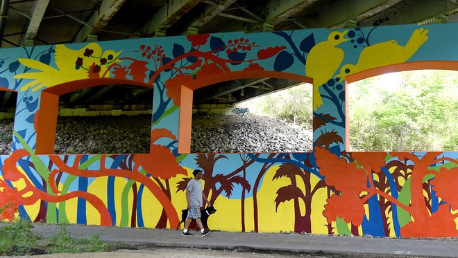 James Gordon of Mansfield walks his dog Bismark up the Richland B&O Trail while admiring the finished mural under the 4th Street Bridge.