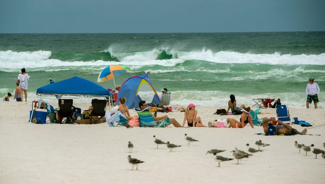 Visitors enjoy Pensacola Beach Sunday, May 27, 2018. Red flags were flying at Pensacola Beach keeping people out of the gulf because of high surf and rip currents.