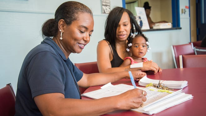 Lisa Hyde-Miller, community relations coordinator for the Villages at Roll Hill, helps Keirra Evans, of Villages at Roll Hill, sign her children up for free backpacks with school supplies July 6.