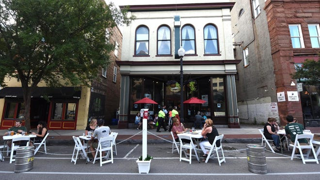 Customers sit outside in the street Thursday June 25, 2020 at Front Street Brewery in Wilmington as Downtown Alive, a program to help restaurants during the pandemic, begins. [STARNEWS FILE PHOTO]