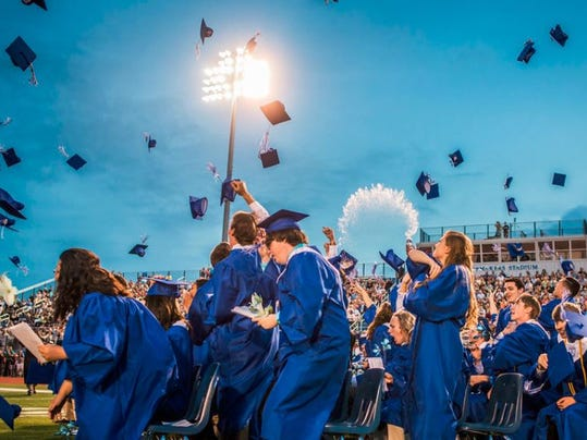 Spring Grove Area High School graduates toss their caps into the air amidst a spray of water at the conclusion of their commencement ceremony at Papermakers Stadium on Friday, June 5, 2015.