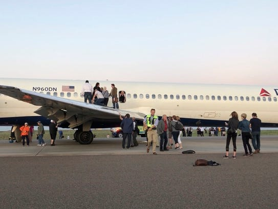 Passengers exit a plane and stand on the tarmac of Denver International Airport after being evacuated from a Delta flight from Detroit on Tuesday May 8, 2018.